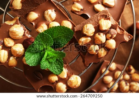 Chocolate with nuts and mint on metal stand, closeup - stock photo