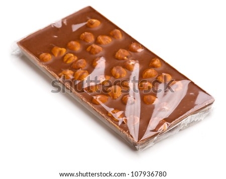 Chocolate with nuts wrapped in transparent foil. - stock photo