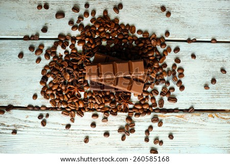 Chocolate with star anise and coffee beans on wooden background - stock photo