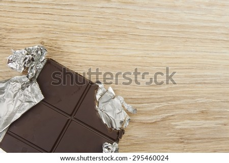 Chocolate wrapped in aluminum foil on a wooden board. Wrapped sweet treat. - stock photo