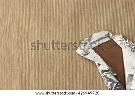 Chocolate wrapped in aluminum foil on bright tablecloth. Advertising on chocolate. Sales chocolate . Packing chocolate. Chocolate shop. Sweet chocolate bar. - stock photo