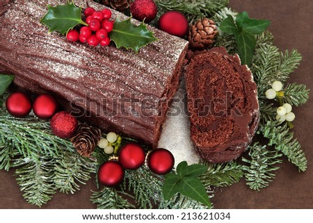 Chocolate yule log cake with red bauble decorations, holly, ivy, mistletoe and snow covered fir over brown handmade lokta paper background. - stock photo