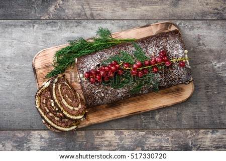 Chocolate yule log christmas cake with red currant on wooden ...