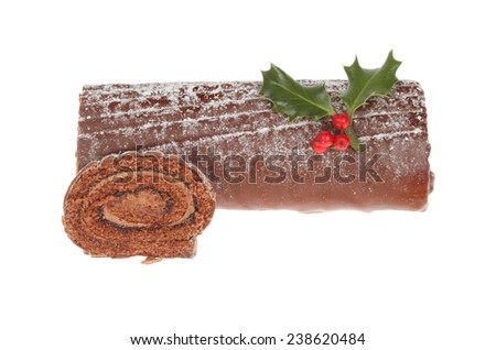 Chocolate yule log decorated with holly and a cut slice isolated against white - stock photo