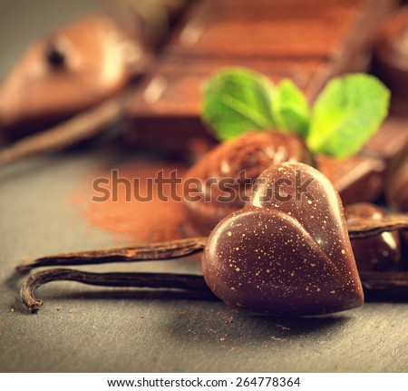 Chocolates background. Chocolate. Assortment of fine chocolates in dark and milk chocolate with vanilla and mint. Praline Chocolate sweets. Heart shaped - stock photo