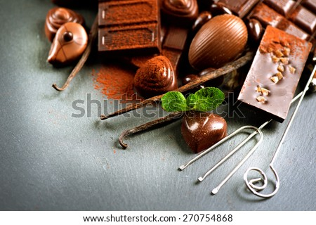 Chocolates background. Chocolate. Assortment of fine chocolates in dark and milk chocolate with vanilla and mint. Praline Chocolate sweets - stock photo