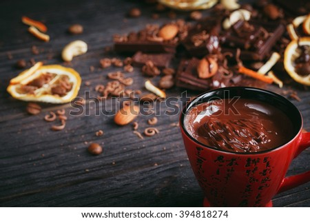 Chocolates background. Chocolate. Cup of hot chocolate, lemon, nuts and assortment of fine chocolates in dark, and milk chocolate on dark wooden table - stock photo