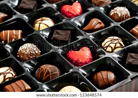 chocolates in a box, with red love heart shaped chocolate - stock photo