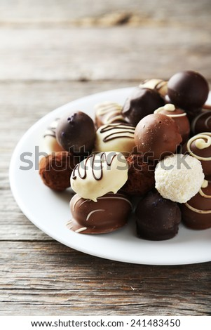 Chocolates on plate on grey wooden background - stock photo