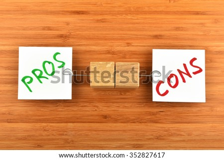 Choice, dilemma, two white paper notes with marker written pros and cons words, wooden holders in different directions on bamboo wooden background for presentation