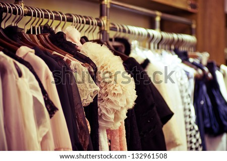 Choice of fashion clothes of different colors on wooden hangers - stock photo