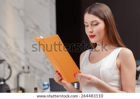 Choice of the drink. Young attractive brunette looking through the menu while sitting at the counter of the bar  - stock photo
