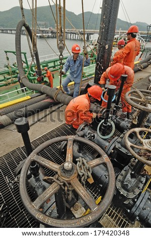 CHONBURI - OCTOBER 3: Workers preparing for loading crude oil form ship to taker in Chonburi, Thailand on October 3, 2008.  - stock photo