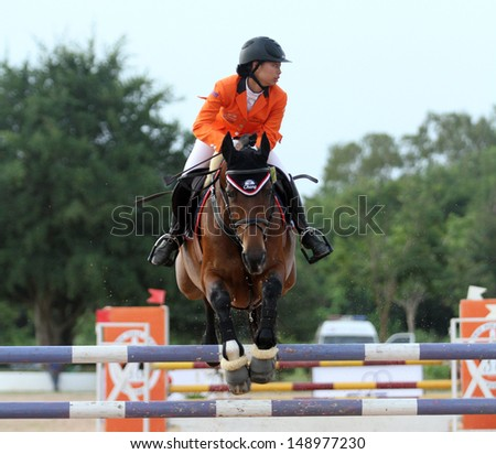 CHONBURI, THAILAND - JULY 27:Siengsaw Lertratanachai of Thailand with Elmo BB in action during FEI World Jumping Challenge 2013 at Thai Polo&Equestrian Club on July 27, 2013 in Chonburi, Thailand. - stock photo