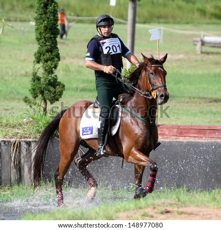 CHONBURI, THAILAND - JULY 27:Singh Sangram of India with Yontrakan in action during 1st FEI Asian Eventing Championships 2013 at Thai Polo&Equestrian Club on July 27, 2013 in Chonburi, Thailand. - stock photo