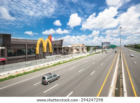 CHONBURI-THAILAND - JULY 6 : The wide lanes with high speed cars and Mcdonalds restaurant building on the motorway from Bangkok to Pattaya on July 6,2015  - stock photo
