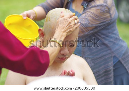 CHONBURI, THAILAND - JUNE 15 : Thai man shower by a parent during a Buddhist ordination ceremony on June 15, 2014 in Chonburi, Thailand. - stock photo