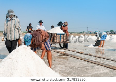 CHONBURI, THAILAND - MAR 11: Unidentified workers carrying salt at salt farm on March 07, 2010 in Chonburi Thailand. Chonburi is the main industrial area in Thailand - stock photo