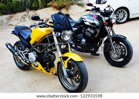 CHONBURI, THAILAND - NOVEMBER 18 2016 : Yellow motorcycle brand Ducati Monster and Black motorcycle brand Honda CB400, 400CC at the home Chonburi in Thailand.