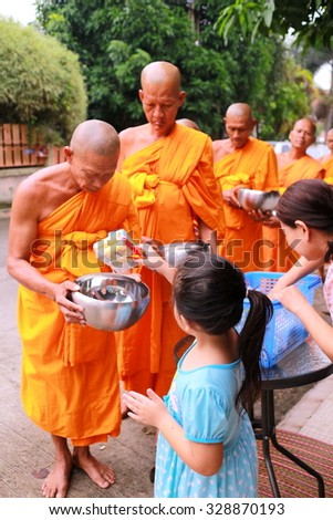 Chonburi, THAILAND - October 18 2015: Buddhist give food offerings to a Buddhist monk in morning at Nuchanard village road Thailand
