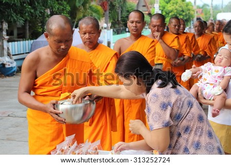 Chonburi, THAILAND - September 05 2015: Buddhist give food offerings to a Buddhist monk in morning at Nuchanard village road Thailand. - stock photo