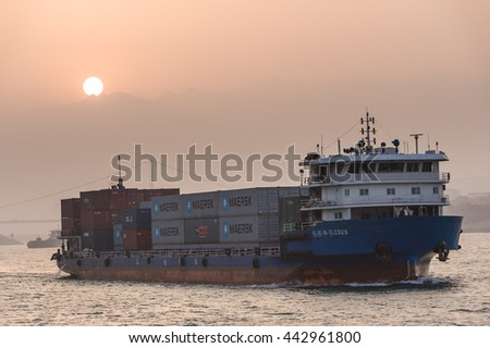 Chongqing, China, 18 Nov 2012: Industrial container ships sailing along river during sunset.