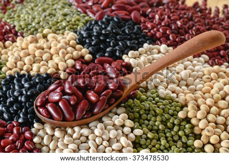 Choose a red bean on wooden spoon on multicolor lentins background