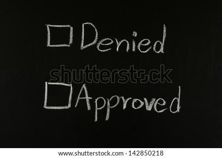 choose approved or denied written on blackboard - stock photo