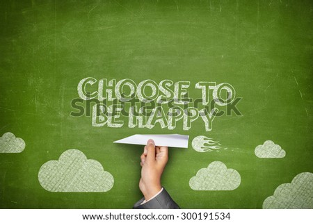 Choose to be happy concept on green blackboard with businessman hand holding paper plane - stock photo