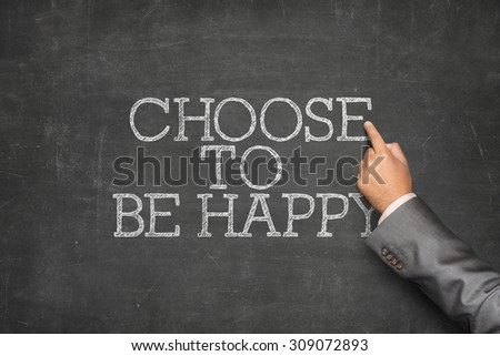 Choose to be happy text on blackboard with businessman hand pointing
