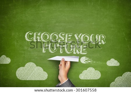Choose your future concept on green blackboard with businessman hand holding paper plane - stock photo