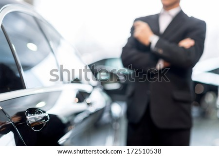 Choosing a car at dealership. Thoughtful grey hair man in formalwear leaning at the car and looking away - stock photo