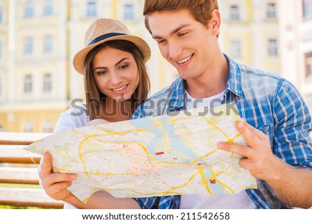 Choosing a nice place to visit. Happy young tourist couple sitting on the bench together and examining map  - stock photo