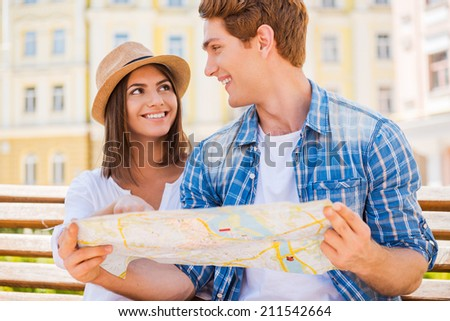 Choosing a place to go. Happy young tourist couple sitting on the bench together and examining map  - stock photo