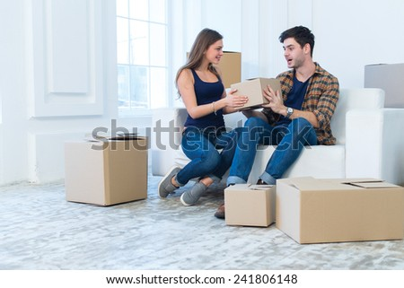 Choosing box for unpacking in new house. Young and beautiful couple is moving to new apartment surrounded with plenty of cardboard boxes