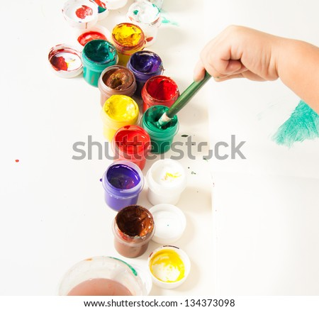 Choosing colors for first drawing - close-up of paint buckets with kids hand and paintbrush - stock photo