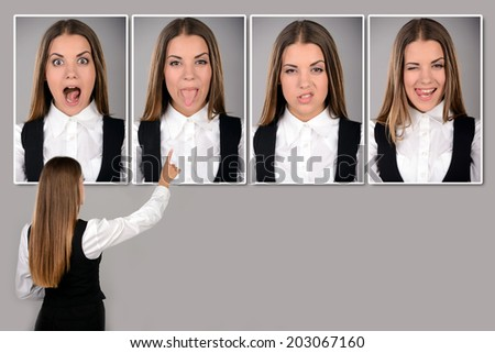 Choosing emotions. Business woman looking at the portraits of different emotions. - stock photo