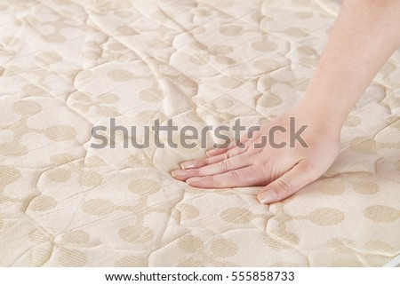 choosing mattress and bed closeup of female hand touching and testing mattress in