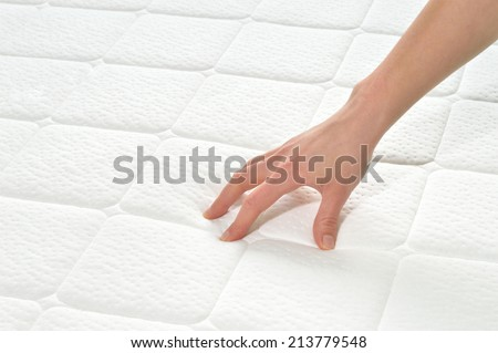 Choosing mattress and bed. Close-up of female hand touching and testing mattress in a store. Copy space. - stock photo