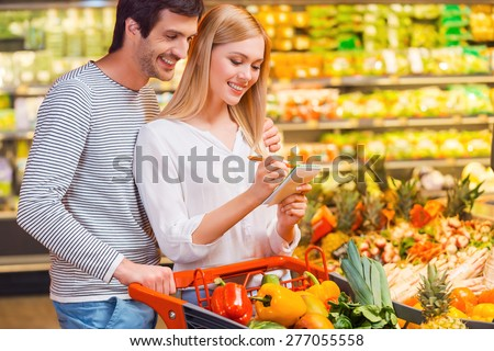 Choosing only healthy food. Happy young couple bonding to each other and smiling while shopping in a food store - stock photo