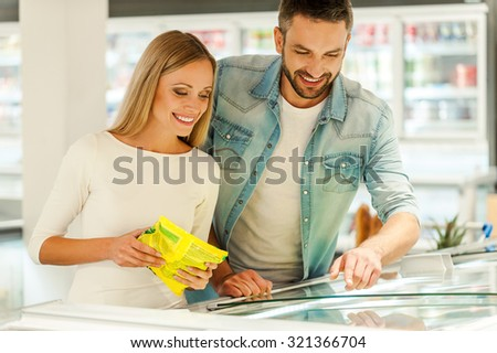 Choosing products for dinner. Happy young couple choosing products together while standing near refrigerator in a food store - stock photo
