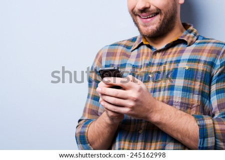 Choosing right words. Close-up of handsome young man in shirt holding mobile phone and smiling while standing against grey background - stock photo