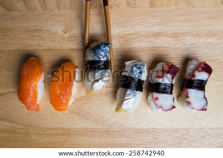 Choosing sushi by chopsticks on wood background - stock photo