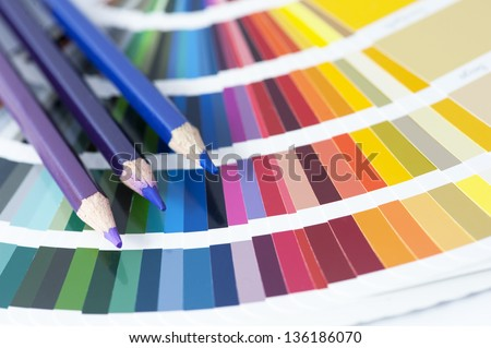 choosing the color from the spectrum - open pantone color card with three pencils - stock photo