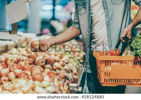 Choosing the freshest apples. Close-up of young man holding apple and shopping bag while standing in a food store - stock photo
