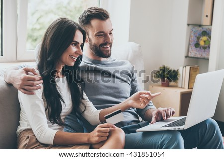 Choosing what to get. Beautiful young woman holding credit card and pointing laptop with smile while sitting together with her husband on the couch  - stock photo