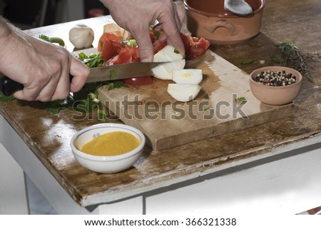 Chop celery, tomato, onions on a wooden cutting board for cooking. - stock photo