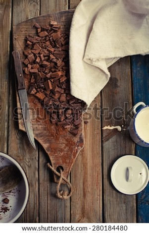 Choped chocolate over rustic cutting board with milk cream and linen napkin. Ingredients to prepare chocolate homemade. Top view.  - stock photo