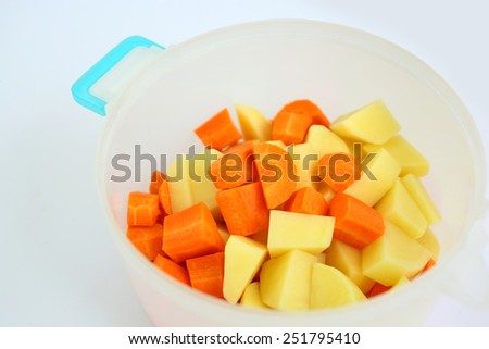 Chopped and sliced carrot and potatoes in plastic pot - stock photo