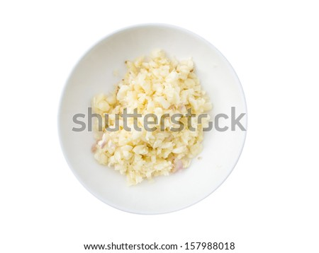 chopped and slices of garlic in white bow on wooden table - stock photo